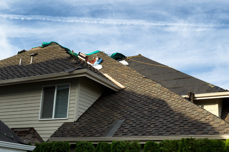 tar felt: Home with roof being replaced showing new shingles, felt paper, and tools. Blue sky in background.