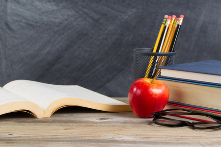 wooden desk: Desktop with books, red apple, reading glasses, and pencils in front of blackboard. Layout in horizontal format with plenty of copy space. Stock Photo