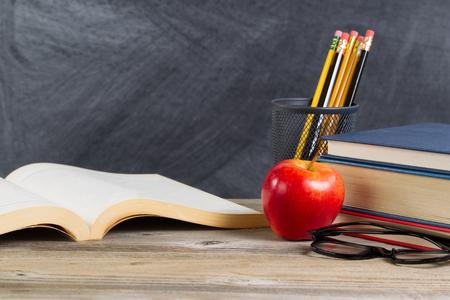 Escritorio con libros, manzana roja, gafas de lectura, y lápices en frente de la pizarra. Disposición en formato horizontal con un montón de espacio de la copia. Foto de archivo - 47057791