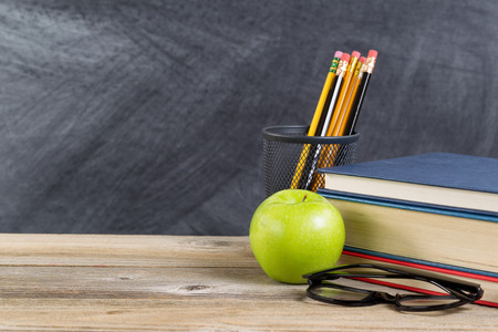 Desktop with reading materials and green apple in front of blackboard. Layout in horizontal format with copy space. Stockfoto