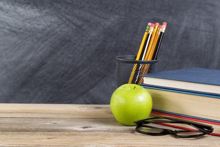 utiles escolares: Escritorio con materiales de lectura y manzana verde delante de la pizarra. Disposición en formato horizontal, con copia espacio.