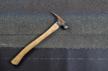 tar felt: Used roofing hammer on new composite shingles and felt paper in horizontal format. Stock Photo