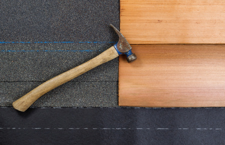 tar felt: Used roofing hammer on new composite and cedar shake shingles with felt paper in horizontal format. Stock Photo
