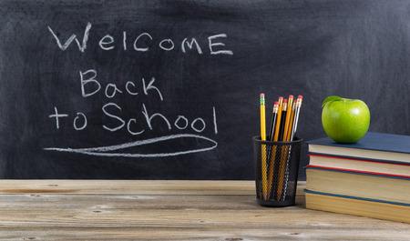bienvenida: Escritorio de madera vieja con útiles escolares básicos y la bienvenida de regreso a la escuela de texto en la pizarra para los estudiantes. Disposición en formato horizontal. Foto de archivo