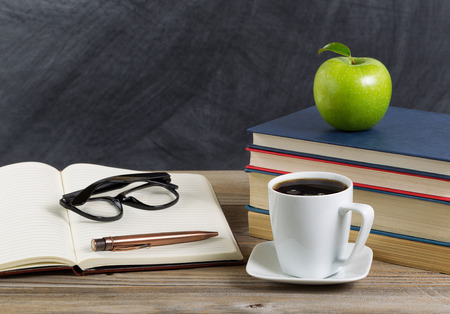 carta e penna: Close up of a rustic desktop of teacher with books, paper, pen, coffee, reading glasses a long with a green apple in front of chalkboard. Layout in horizontal format with copy space.