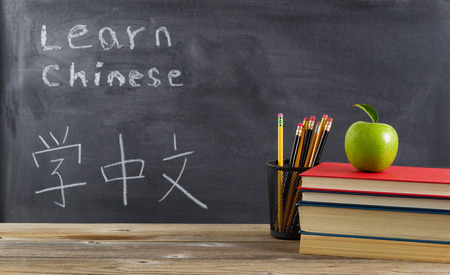 Front view of rustic desk for student learning Chinese with books, pencils and a green apple in front of chalkboard with Mandarin text.