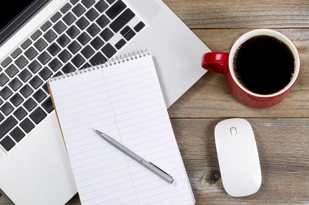 boligrafos: Papel y lápiz sobre portátil con café y el ratón en el lado de la mesa de madera rústica.