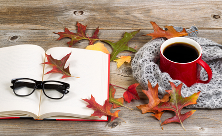 Coffee, autumn leaves, book, reading glasses and grey scarf on rustic wood. Stock Photo