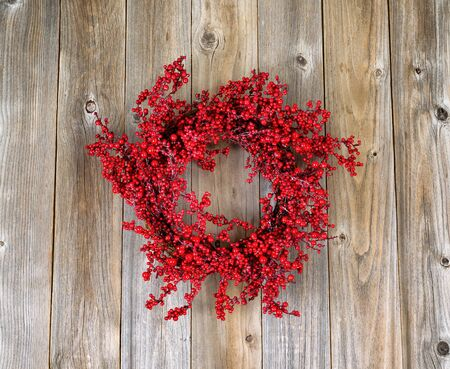 Red holly berry wreath on rustic wood. Boards in vertical layout. Stock Photo