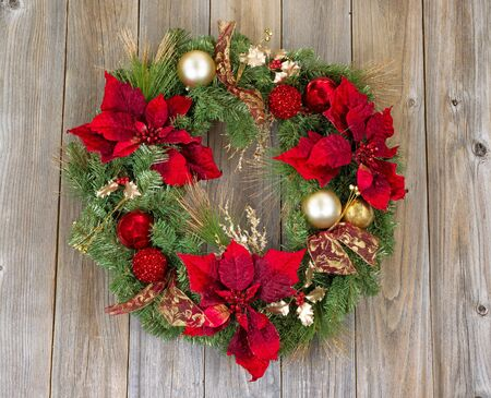 poinsettia: Traditional Christmas wreath on rustic cedar wood. Boards in vertical pattern.