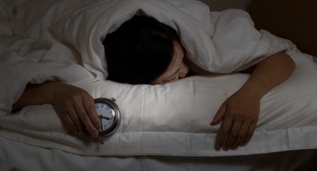 Woman with insomnia, under blanket looking down, holding alarm clock in hand. Select light and focus on woman and clock with darker background for night time concept.