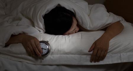 Frau mit Schlaflosigkeit, unter Decke nach unten, mit Wecker in der Hand. Wählen Sie Licht und konzentrieren sich auf Frau und Uhr mit dunkleren Hintergrund für die Nacht-Konzept.