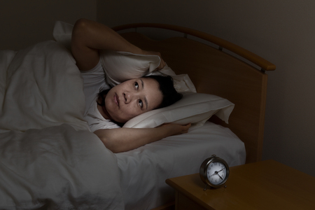 eyes open: Woman with insomnia covering her ears with pillow while eyes open. Select light and focus on woman with darker background for night time concept.