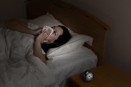 chory: Kobieta wycieranie nosa z tkanki, starając się spać. Wybierz światło i skupić się na kobiety i zegar z ciemniejszym tle. Choroba na koncepcji czasu w nocy.