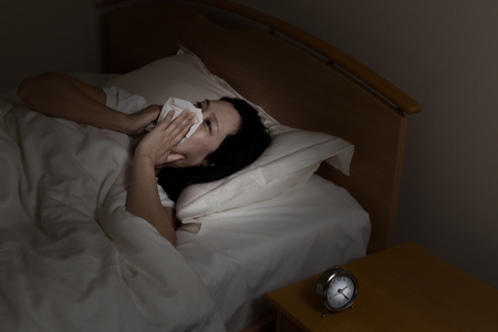 Woman wiping nose with tissue while trying to sleep. Select light and focus on woman and clock with darker background. Sickness at night time concept.