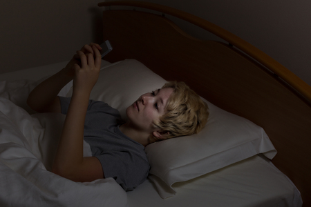 Teenage girl using her cell phone while in bed. Teen using technology late at night instead of sleeping.