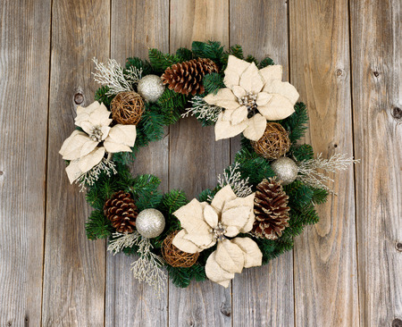 White Poinsettia flower and pine cone Christmas wreath on rustic cedar wood.