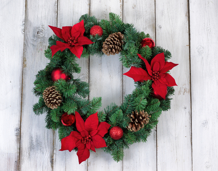 xmas background: Poinsettia flower Christmas wreath on rustic white wood. Stock Photo