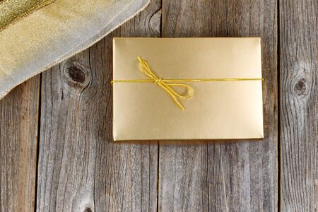 gift ribbon: Golden color wrapped gift box and ribbon on rustic wood. Holiday concept of giving. Stock Photo