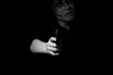 youth crime: Teenage girl with weapon pointing towards camera in dark background. Selective lighting on hand and weapon. Teen violence concept.