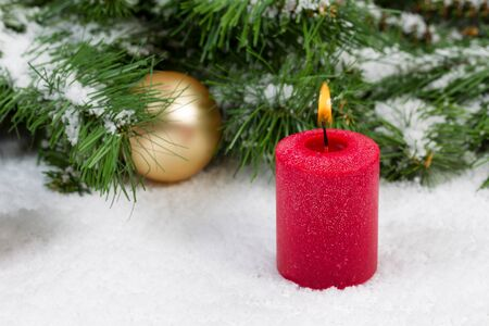 christmas candles: Close up of burning red candle with evergreen branches and gold ornaments covered in snow. Selective focus on front upper part of candle and flame with Christmas concept.