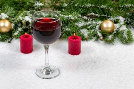 glass of red wine: Close up of a glass of red wine with burning red candles, evergreen branches and gold ornaments covered in snow. Selective focus on front upper part of wine glass with holiday concept.