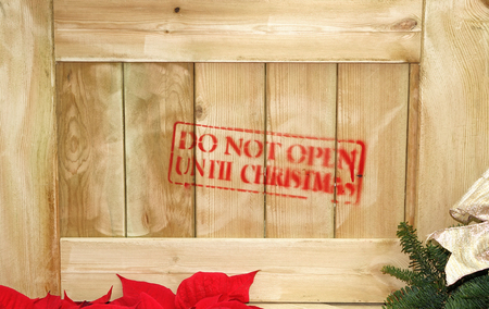 stating: Close up of wooden box with red text stating do not open until Christmas. Partial poinsettia and evergreen. Stock Photo