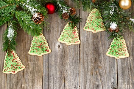 angled view: High angled view of tree shaped cookies with evergreen branches, pine cones, snow and ornaments on rustic wood. Stock Photo