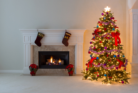 Bright Christmas tree and glowing fireplace in living room. Stock Photo