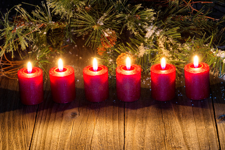 evergreens: Burning red candles with snow covered evergreens and rustic wood. Stock Photo