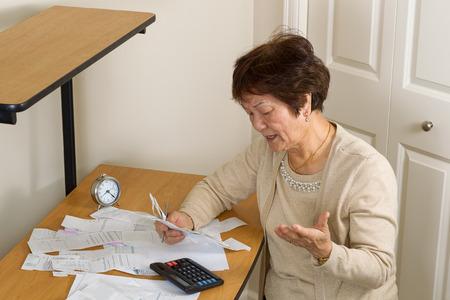 Ältere Frau, die ihre Rechnungen aufgeregt. In Schulden-Konzept.