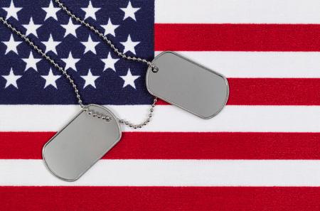 estrellas  de militares: Bandera de los Estados Unidos de América con etiquetas de identificación militares y la cadena del cuello. Foto de archivo