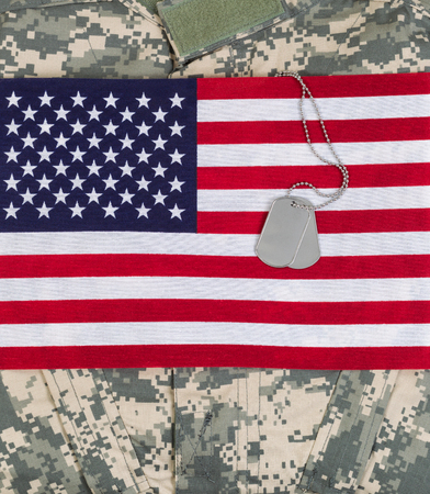 memorial day: United States of America flag, military identification tags, neck chain, and combat uniform top. Vertical layout. Stock Photo