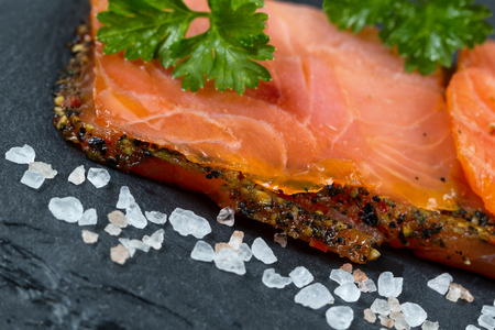 Close up of finely sliced smoked salmon, tilted angle, on natural slate stone with coarse salt. Selective focus on front part of salmon. Stok Fotoğraf