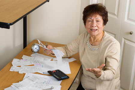 elderly woman: Senior woman expressing extreme anger while working on her financial bills. In debt concept.