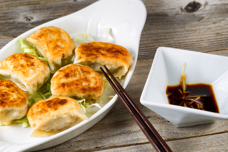 Close up of a front view of Chinese dumpling with sauce in bowl with chopsticks on rustic wood. Selective focus on tip of chopsticks.