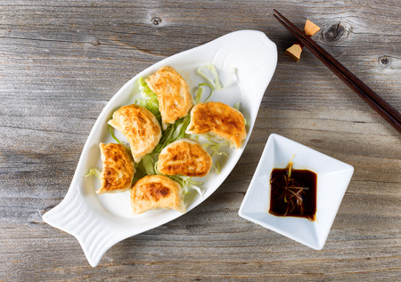 angled view: High angled view of Chinese dumpling with sauce in bowl with chopsticks on rustic wood. Stock Photo
