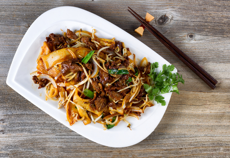 asian foods: Top view of freshly cooked spicy beef, bean sprouts, onion, tofu with parsley as garnish and chopsticks in holder on rustic wood.