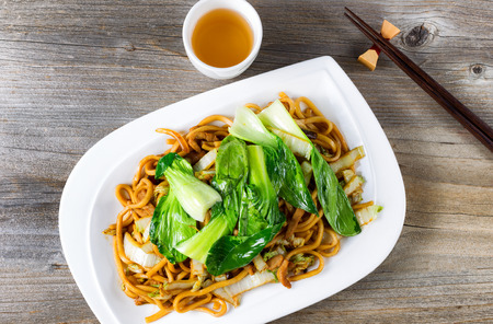 angled view: High angled view of spicy cooked noodles, onion, bok choy, chicken slices, chopsticks and tea on rustic wood.