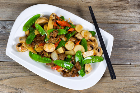 High angled view of Asian dish consisting of sliced juicy beef rice, onion, mushroom, green peas, and red pepper. Chopsticks on side of plate with rustic wood underneath.