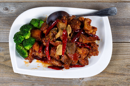 angled view: High angled view of Chinese dish consisting of fried tofu, red peppers, and broccoli. Large serving spoon on side of plate with rustic wood underneath. Stock Photo