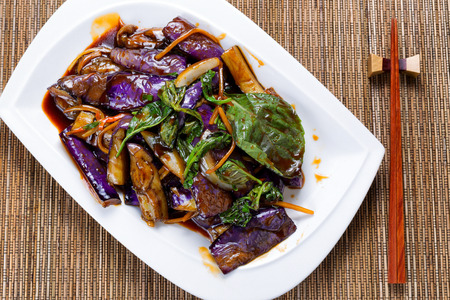 High angled view of cooked eggplant, onion and basil leaves in juicy sauce. Chopsticks in holder with bamboo mat underneath.