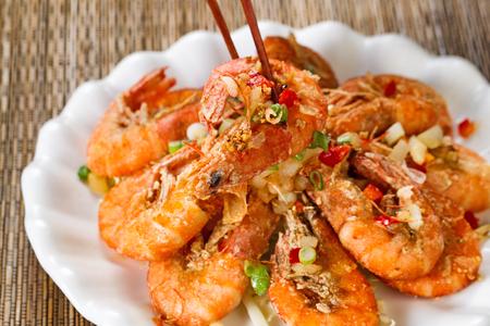 camaron: Cerrar la vista frontal de un camarón frito pan recubierto, el enfoque selectivo en una sola pieza en palillos, con los aderezos frescos.