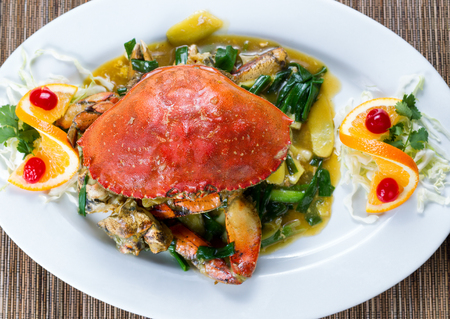 angled view: High angled view of a freshly cooked whole Dungeness crab in green onion sauce on white plate.