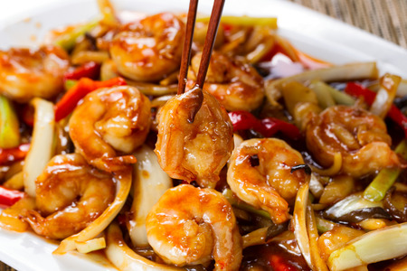 Close up front view of a curry shrimp, selective focus on single piece in chopsticks, with fresh peppers on onion in background. Stockfoto