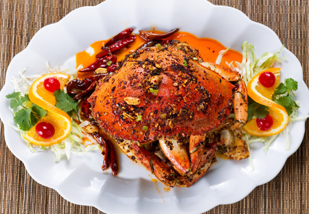 dungeness: High angled view of a freshly cooked whole Dungeness crab covered with peanut sauce, spices and herbs on white plate. Stock Photo