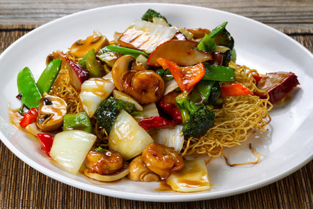 eating noodles: Close up front view of a fried noodle with shrimp, pork, vegetables and sauce in white plate. Stock Photo