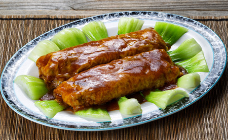 bean curd: Close up front view of a meat wrapped in tofu, sauce on top, with bok choy. Stock Photo