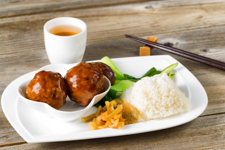 front view: Close up front view Asian saucy meatballs, rice and bok choy on white plate. Chopsticks and green tea in background. Stock Photo