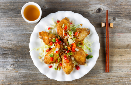 Top view of fried Asian style chicken wings in white plate with garnishes. Green tea and chopsticks in holder. Rustic wooden boards underneath. Banco de Imagens